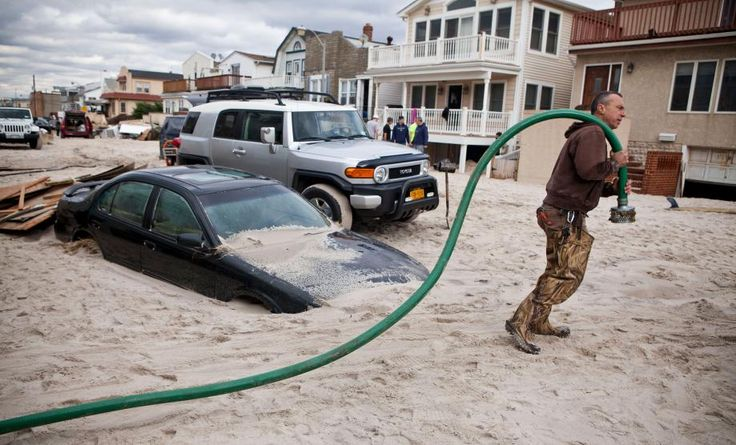 LONG BEACH, NY - OCTOBER 31: Robert Justh drags a hose while attempting to drain a flooded basement, caused by Hurricane Sandy, on October 31, 2012 in Long Beach, New York.The storm has claimed many lives in the United States and has caused massive flooding across much of the Atlantic seaboard. U.S. President Barack Obama has declared the situation a 'major disaster' for large areas of the U.S. east coast, including New York City, with widespread power outages and significant flooding in…