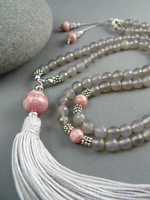 Gemstone mala beads with Rhodochrosite accent bead and 108 Silver Agate beads.  A beautiful shade of silver grey, these translucent facetted natural gemstone Agate mala beads have marker and guru beads of natural Rhodochrosite. Gentle energy for heart and soul, perfect for mantra meditations and affirmation practice.  Total length of mala beads is 28 inches, excluding tassel - long enough to slip over your head if you want to wear it as a necklace. Grey Agate counter beads are 6mm size. Guru…