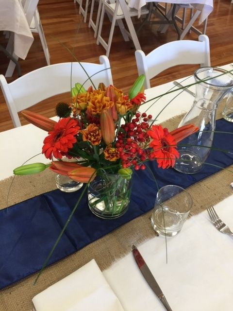 Our burnt orange and blue floral arrangement creates a dramatic table centrepiece