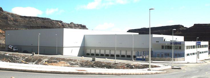 RHENUS TETRANS: Empresa dedicada al transporte y logística.    Nave de 12.000 m2, construido en el año 2008, situado en Las Palmas de Gran Canaria, realizado a base de estructura metálica de Pórticos Armados de sección variable tipo TEKTON, unidos por tornillería de alta resistencia y con una separación entre apoyos de 11,00 mts. Con un ancho de 85 mts., 15 mts. de altura superior de peto, y una pendiente del 7 %. http://www.tekton.es/