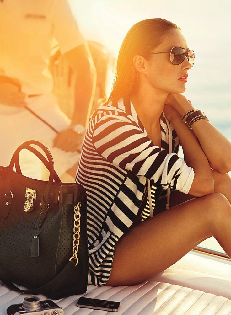 Here Comes the Sun – Face of Michael Kors, model Karmen Pedaru, stars in the brand's summer 2013 catalogue featuring laid-back elegance. The Estonian beauty joins Simon Nessman for a yacht outing wearing a mix of stripes, tropical and psychedelic prints. Accessorized with aviator style sunglasses and ladylike timepieces, Karmen looks ready to vacation in style for the sun-drenched catalogue.