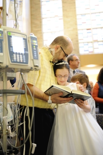 Tim Day kisses his 8-year-old daughter Erin during her first Communion Mass at Strong Memorial Hospital in Rochester, N.Y., April 26. Day is confined to the hospital as he awaits a heart transplant so special arrangements were made for Erin to receive her first Communion from Retired Bishop Matthew H. Clark of Rochester in the hospitals Interfaith Chapel. (CNS photo/Mike Crupi, Catholic Courier)