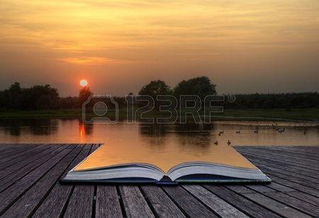 Concetto creativo di bella immagine semplice del tramonto attraverso treccia riflette nel lago in primo piano che esce di libro magico di cui aperto photo