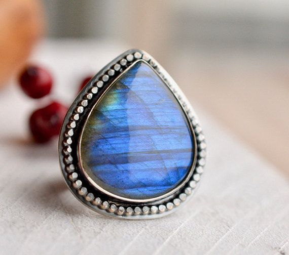This one of a kind ring has been handcrafted of 925 sterling silver and a gorgeous blue fire labradorite cabochon. The stone is flanked by beaded wire which frames the bezel. The ring shank has been textured with a modern design. Handmade by me in beautiful south Denmark,  The width of the band measures 12mm.  Ring face measures 38mm x 34mm.  Size: 9 US. Fits like a size 8.5 US due to the wide band. Can be sized up a 1/2 size if requested.  Stamped on the inside and the back with my make...