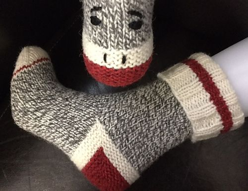"""These adorable socks are cast on at the cuff and include a 'clean' stripe plus a turning round in the ribbing. For the traditional sock monkey look, 3 colours of Briggs & Little 'Tuffy"""" are required, but there will be lots of red mix and ecru left over! (For the main colour, Granite, I used about 65% of the skein for my ladies' small socks.)"""