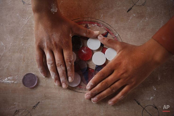 In this Wednesday, July 8, 2015 photo, a boy arranges disks for a game of carrom during break time at a school in Kathmandu, Nepal. (AP Photo/Niranjan Shrestha)