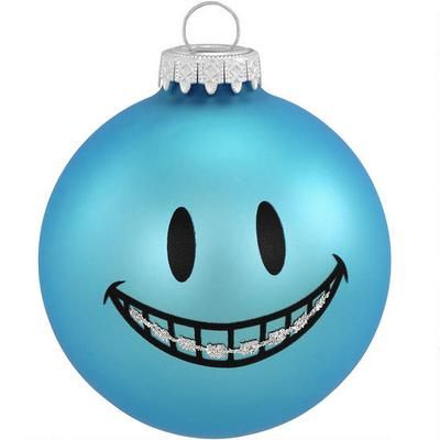 """Working their way to a perfect smile, your loved ones will have to brace themselves when they receive this perfect keepsake! Exclusively crafted for Bronner's from glass in Hungary, our 3"""" tall ornament features a smooth blue finish with a smiling face wearing brilliant braces that shine in glistening glitter. Our blue smile face with braces ornament is sure to put a beautiful toothy grin across the face of friends and family!"""