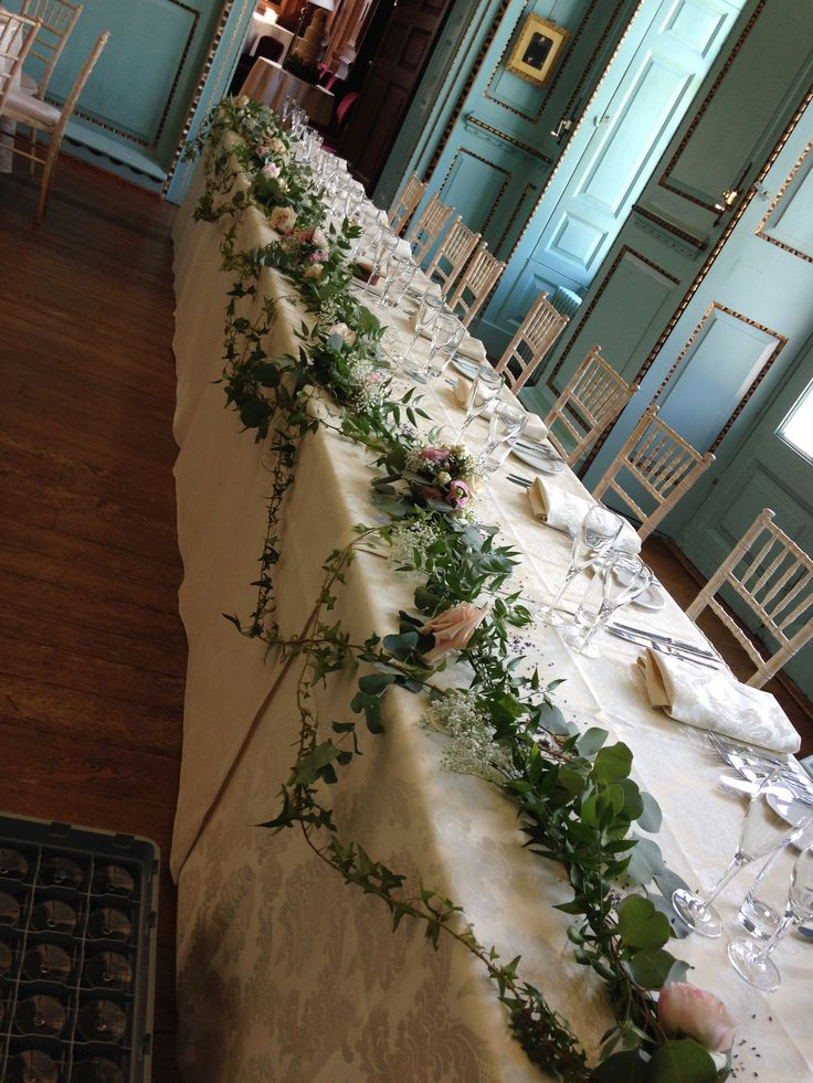 Unusual top table design of Ivy and Eucalyptus with Roses and Snowberries