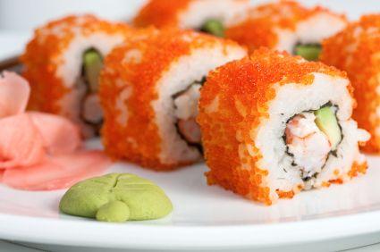 El rollo de sushi California esta relleno de aguacate, cangrejo, pepino y cubierto de masago.