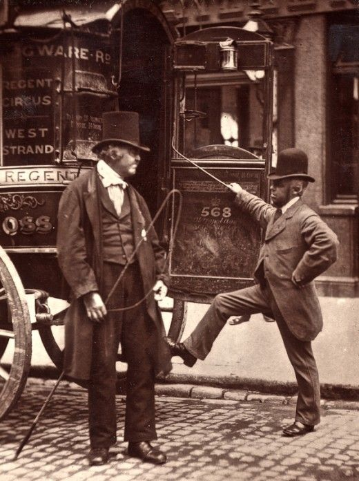 Street life in London, 1876.  Man on the left (with very cool high hat) has horse whip in his hand, so assume he's the carriage driver. Man to the right, maybe an assistant? In any event, it seems like every man at this time period wore a high hat......