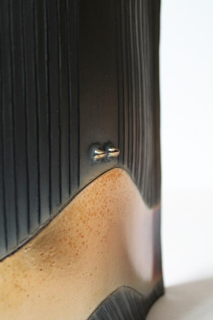 Particolare di un vaso ornamentale realizzato in bucchero, la banda dorata viene messa in risalto dal nero opaco dell'oggetto.
