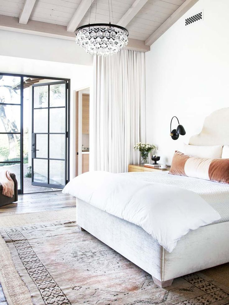 Master bedroom with modern crystal chandelier and black sconces - how to choose bedroom lighting on Thou Swell @thouswellblog