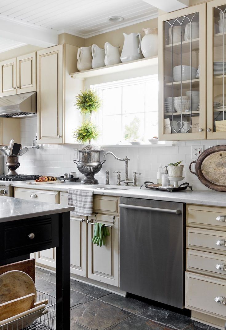Creamy kitchen cabinets and walls paired with white marble counters, slate  floors and white subway