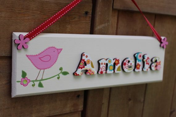 A beautiful handcrafted, wooden name plaque 3D lettering. The lettering has been decorated in a gorgeous multicoloured flower pattern and has a varnished finish. Sequins and beads have been added to the illustrations to make them extra gorgeous. Each plaque is hung by ribbon, with a cute button detail. However, if you would prefer no ribbon and button detail then please specify and double sided foam tape will be provided for mounting.  Please let us know the name you would like on your…