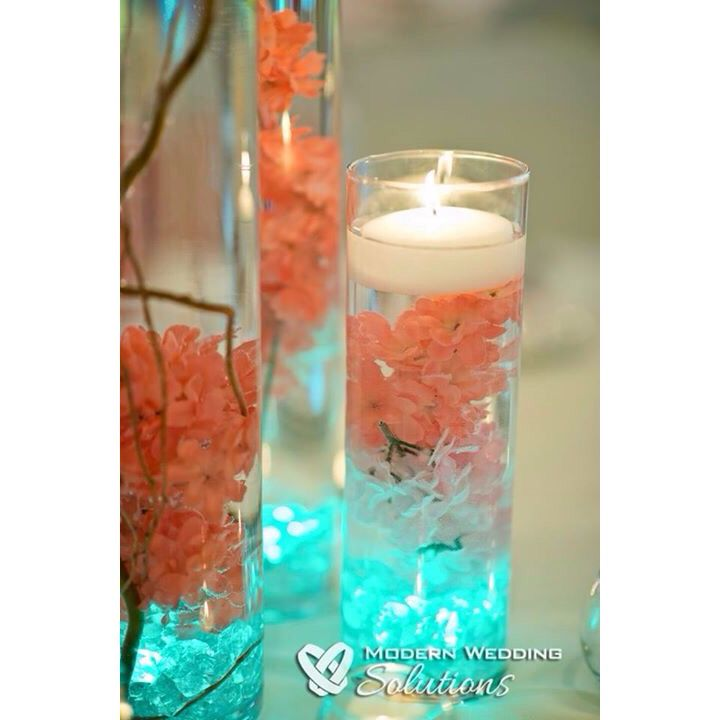 Centerpieces | Coral Hydrangeas | Curly Willow | Teal LED Lights | Floating Candles | Cylinder Vases | See more on our Instagram and Facebook page: @aperfectpetal!