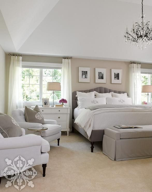 Chic bedroom features a sand colored accent wall lined with three black and white photos over a gray velvet bed dressed in monogrammed bedding flanked by white dressers as nightstands and oval glass lamps placed under windows covered in white drapery panels. Chic master bedroom boasts a small sitting area filled with gray roll arm chairs lined with gray medallion pillows flanking an antiqued mirrored top accent table.