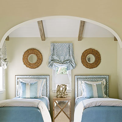 Petite twin bedroom with pale blue and white stripes and zebra print fabric, exposed beams, mirrored side table and casual window treatment