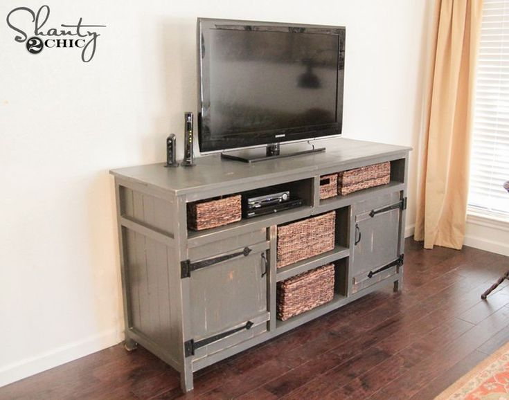 A distressed gray TV stand in a farmhouse style.