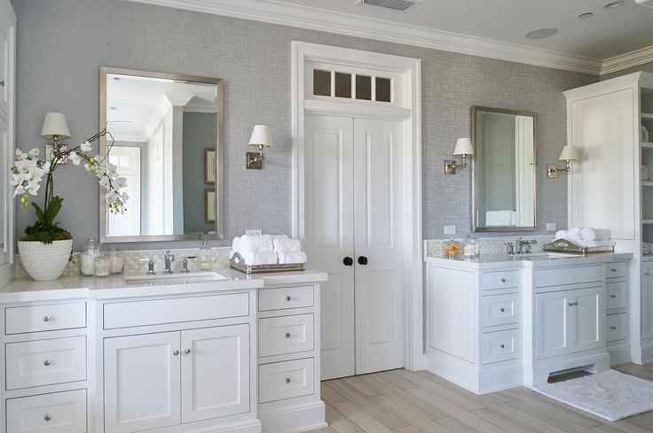 His and her vanities in a large master bathroom. White vanities with chrome fixtures and wallpaper.