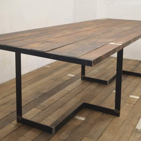 Big handcrafted industrial table, reclaimed wood top and metal legs. Loft style. Dining room. Restaurant table.