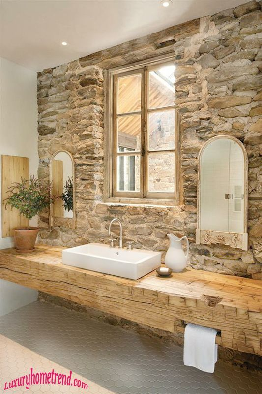 I really like how this integrates stone and wood and yet is light feeling.  Those mirrors would have to go though - Chara.        Sandstone wall cladding rubble construction coupled with an organic weathered timber bench top helps create a stylish rustic bathroom.