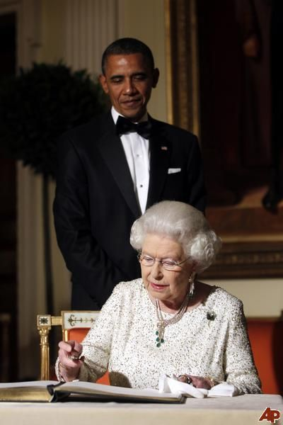 Second Visit May 2011 US 44th President Barack Obama looks on as Britain Queen Elizabeth II signs a guest book after a reciprocal dinner at the Winfield House in London, on May 25, 2011.