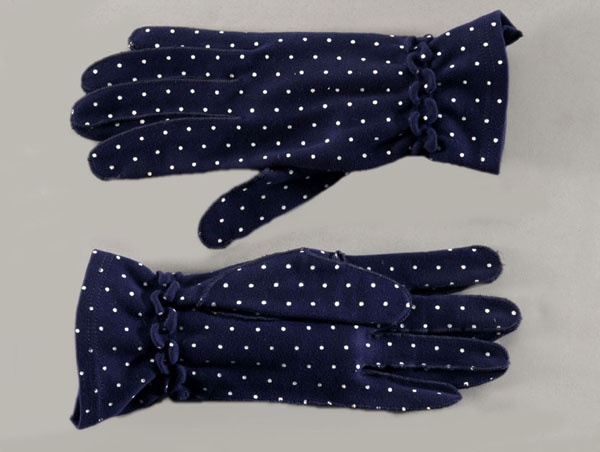A pair of dark blue women's cotton jersey wrist-length gloves with an all over printed pattern of white dots, 1948-52.