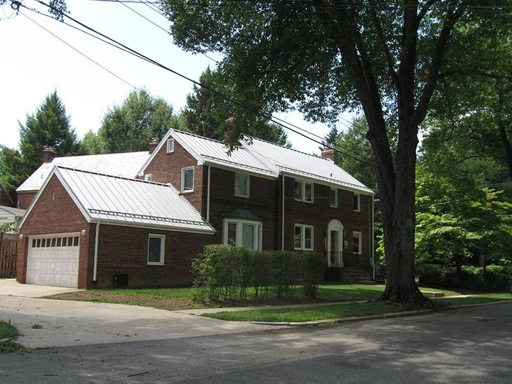 Red brick house with a white standing seam metal roof for Metal roof pictures brick house