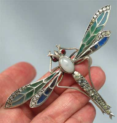 """French Sterling Plique-à-Jour Dragonfly Pin  A spectacular example of antique French plique-à-jour enamel, this sterling dragonfly is a showy 3 5/16"""" wide x 2 1/16"""" tall. The outstretched wings are enameled in rich hues of greens and blues, accented with paste stones, the body has a paste opal in the center and more paste stones down the tail. Finished with red paste eyes, it is marked with the French boar's head for silver. circa.1900"""