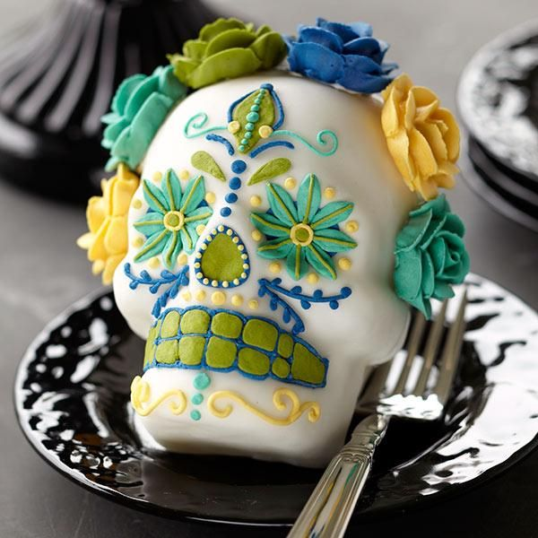 Day of the Dead Mini Cakes - Flowers are thought to attract souls on this ritual holiday, celebrated October 31 through November 2. Here, Wilton Roses in five shades crown a stand-up skull cake baked in our Dimensions 3-D Mini Skull Pan.