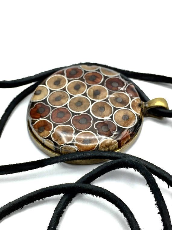 This one of a kind #2 pencil pendant, necklace is made by slicing a block of laminated pencils. The slice is exposes a cross section of the lead and the steel barrel that holds the erasers from inside the wood. Looks like a modern painting The slice is then sanded, coated and domed with