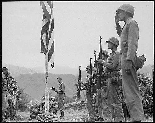 """Lieutenant Colonel John Hopkins, commanding officer of the First Battalion, Fifth Marine Regiment, leads in singing the """"Star Spangled Banner"""" during Memorial Services held in the field during the Korean campaign. (circa June 21, 1951)"""