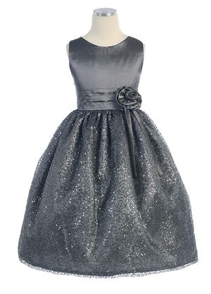 While this gorgeous dress has a simple satin bodice, the skirt more than makes up for it with its stunning mesh sequin overlay that sends sparkles in every direction. The waist is adorned with a beautiful flower. The dress is available in charcoal, off white and plum.