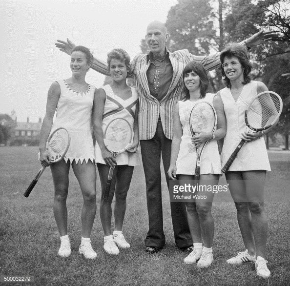 1973 - English fashion designer Ted Tinling (Center), with tennis players wearing his Dacron fashions at the Royal Garden Hotel, Kensington, London. Left to right: Virginia Wade in a dress with shark's teeth details, Evonne Goolagong in a dress with a sweetheart neckline and orange and yellow inset panels, Rosemary Casals in a dress with butterfly motifs, and Billie Jean King in a dress with a diagonal motif in lilac. (Michael Webb/Keystone/Hulton Archive/Getty Images)