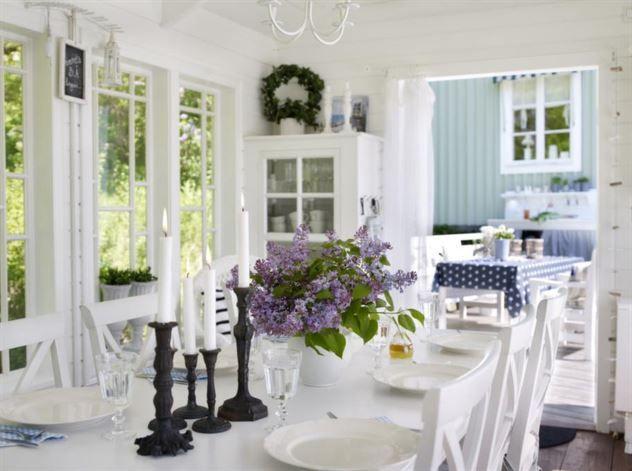 ÖPPET<br>De vackra fönstren skapar magi i lusthuset. Matbord och stolar, Rowico, ljuskrona från Saras mamma, rep med snäckor och drivved, köpt i Kungshamn Bohuslän. Platsbyggt vitrinskåp med dörr av gammalt fönster - inköpt på Östregårds Antik - är Saras idé.