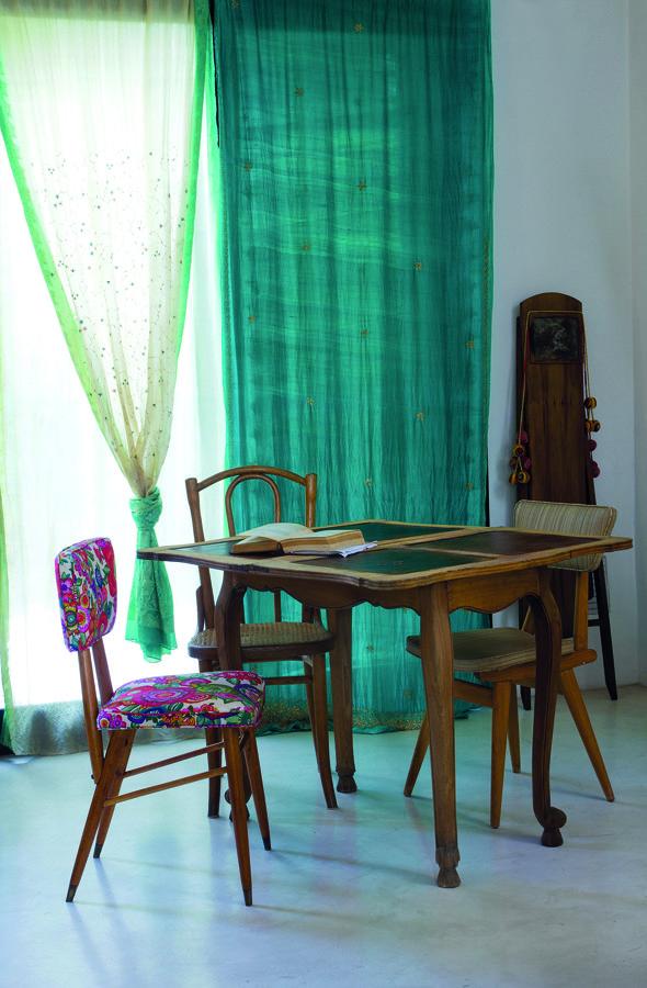 El comedor, que se ubica junto al living, se resume en esta mesa provenzal de formato cuadrado, acompañada por sillas de diferentes estilos (Boulevard Sáenz Peña) retapizadas y restauradas por Betina. Detrás, los ventanales que dan al patio, todos con cortinas bordadas en color verde aqua (Allegra Casa). Una antigua tabla de planchar (Boulevard Sáenz Peña) aguarda a un lado