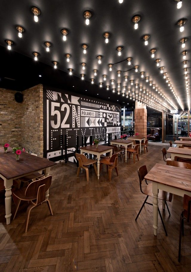 ::LIGHTING::  52 North Bar and Kitchen in Soho London decorated by 44th Hill.  A runway of lightbulbs that runs vertical through the space and directs you to the bar.  It gives the hint of a nightclub without being too much.  Balanced perfectly with the interior brick walls, wooden interior and graphic design elements.  Note the classic Eames chairs and Chesterfields.
