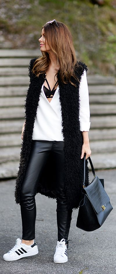 Annette Haga is wearing a black faux fur vest from Asos, white shirt from Cameo, black leather pants from H&M Trend, black and white sneakers from Adidas and the black bag is from Céline