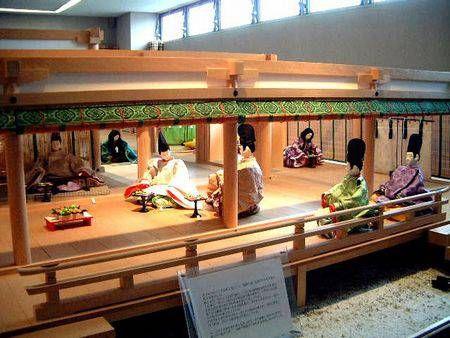 京都市下京区にある風俗博物館のこと。2001年2月に風俗博物館にて撮影。『源氏物語』<若菜上>より蹴鞠の後の宴の様子です。六條院春の町で蹴鞠が行われたあと宴となりました。紫の上が住む東の対が舞台です。高坏には椿餅、梨、柑子のようなもの、干物が並んでいます。写真左から光源氏・夕霧・柏木。若者たち。御簾の奥では、女房たちが宴の準備に大忙し。この写真の奥にちらりと見えるのが紫の上です。紫の上は樺桜の小袿、紅梅のかさねを着ています。桜の枝をかざる女房。束帯の着装順序へ続きます。<コメントをくださる方は掲示板へ。>web拍手ボタン☆チェック!:Amazon/源氏物語の関連本