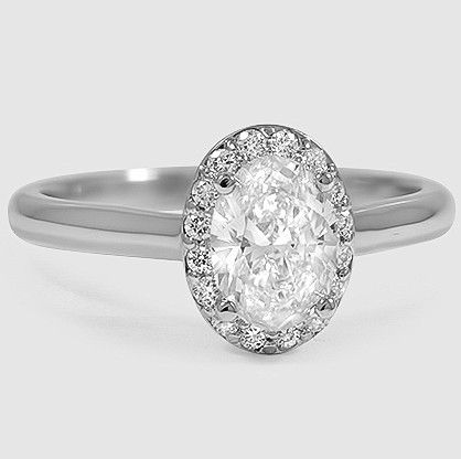A halo of pavé-set diamonds embraces the oval shaped diamond in this brilliant antique-style ring.