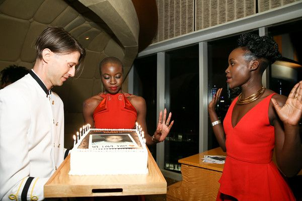 Actress Danai Gurira blows out the candles on her birthday cake as Lupita Nyong'o (R) looks on during the DANAI x One x Love Our Girls celebration at The Top of The Standard on February 12, 2018 in New York City. - DANAI x ONE x LOVE OUR GIRLS Celebration