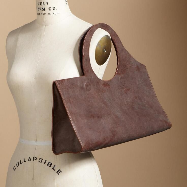 Sculptured swag bag in unlined, vegetable-tanned leather, hand aged to a deep tan patina, asymmetrically cut with a circular handle, closed with double...