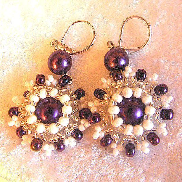 """Náušnice je ve tvaru květinky o velikosti 2,5 cm, celková velikost 3,3 cm. Vyrobeno ze 2 ks tmavě fialových voskovek, rokajlu v barvě stříbrná, bílá perleťová a peričky 3 mm. Náušnice je na zaklapávací zapínání. Hodí se k náramku """"Šněrovačka""""."""