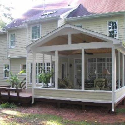This open porch looks like it has been there forever! With its matching siding and white accents, the new structure seamlessly joins the house. The porch is open to a small deck with additional seating for guests.