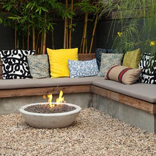 Bench seat with cushions for cosy garden corner.