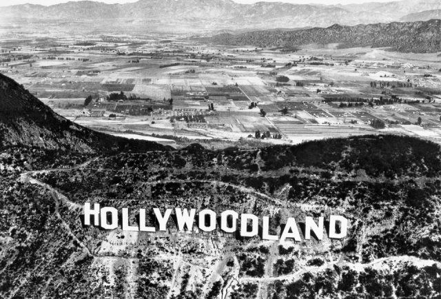 """(ca. 1920s) - The HOLLYWOODLAND sign was erected in 1923 to advertise a new housing development in the hills above the Hollywood district of Los Angeles. In 1949 the Hollywood Chamber of Commerce contracted to repair and rebuild the sign. The contract stipulated that """"LAND"""" be removed to reflect the district, not the housing development."""