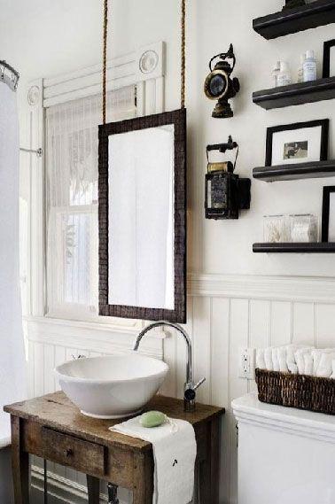 Dans une salle de bain rétro le plan vasque est aménagé avec un petit meuble bois relooké avec un vernis de protection