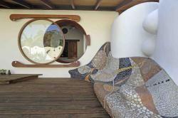 Ventana redonda que abre rodando junto a sillon de mosaico con piezas realizadas a mano