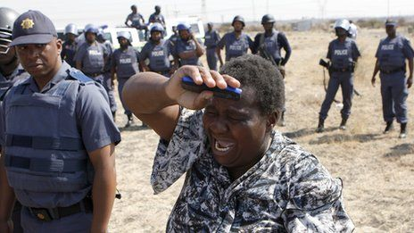 Marikana: A year on | A woman cries as she confronts a police officer during a protest against the killing of miners by South African police.