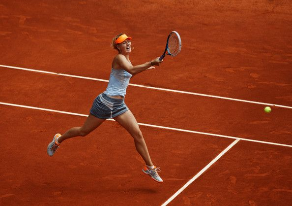 Maria Sharapova Photos Photos - Maria Sharapova of Russia jumps to play a forehand to Sabine Lisicki of Germany on day six of the Mutua Madrid Open tennis tournament at the Caja Magica on May 9, 2013 in Madrid, Spain. - Mutua Madrid Open: Day 6